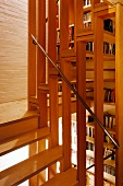 Wooden staircase with stainless steel handrail in open-plan stairwell