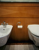 Wall-hung bidet and toilet on wood-panelled wall