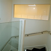 Stainless steel handrail on wall and illuminated window in white stairwell