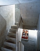 Concrete stairwell with illuminated film poster on wall