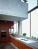 Kitchen counter in front of glass wall beneath floating concrete gallery