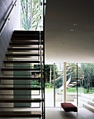 Staircase with wooden treads in open-plan living room and view of exterior stairs though terrace window