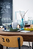 Dining room with plates and cups on wooden table, crockery on surface in background and large blackboard