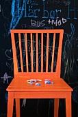 Orange chair in front of blackboard