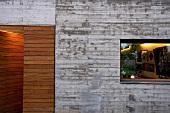Zeitgenössische Hausfassade im Stil des Brutalismus mit Langfenster und holzverkleidetem Eingang