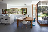 Modern kitchen and dining area with slate floor and glass wall leading to terrace