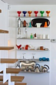 Colourful, postmodern kitchen utensils on stainless steel kitchen shelves