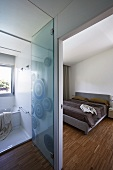 View into modern bedroom with strip parquet, glass door and ensuite bathroom