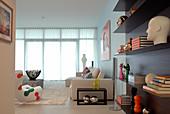 Wohnzimmerdeko mit modernen Designobjekten - elegant schwebendes Wandregal und helle Sitzgruppe im Hintergrund