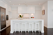 Designer kitchen with white island and retro bar stools