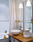 White basin on wooden surface in front of mirror in modern bathroom