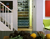 Staircase in kitchen and view of wine rack through doorway