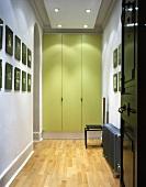 Hell beleuchteter modernisierter Flur mit Einbauschrank und grünlackierten Türen