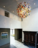 Double-height, open-plan foyer with designer pendant lamp and antique wooden cupboard
