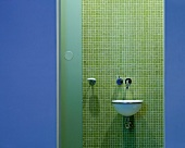 View of designer wash basin on wall with green mosaic tiles through open door