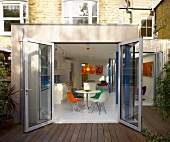 Extension with wooden terrace and open glass door with view of modern dining area