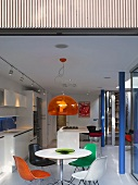 Dining area with colourful shell chairs and pendant lamp with orange glass shade