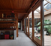 Living space with wood-panelled walls and ceiling and view of adjacent room through open sliding door