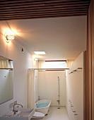 View into white bathroom with shower and bath area separated by curtain