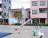 Children's playground in front of modern houses and contemporary house with large window