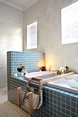 Blue-tiled bathtub with half-height partition in simple bathroom