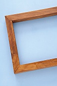 Mahogany-coloured wooden frame on blue background