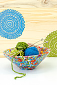 A wooden bowl covered with colorful paper with a knitted pattern; inside balls of wool and knitting needles