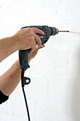 DIY - man drilling hole in wall