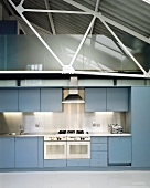 Light-grey fitted kitchen in loft apartment