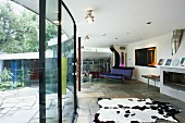 Curved glass wall on stone floor between terrace and modern living space with cow skin rug and rocking sofa