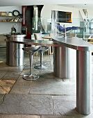 Stainless steel, freeform, designer kitchen with stone floor and silver retro bar stools at kitchen counter