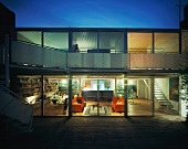 Twilight view of illuminated, contemporary living space with orange sofas and bookcases