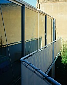 Reflections in glass facade of contemporary house behind stretched canvas balustrade