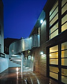 Contemporary house at dusk - steel spiral staircase and wet wooden flooring in illuminated courtyard