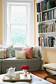 Afternoon tea in reading corner with scatter cushions on upholstered sofa and tray with posy
