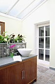 Modern ensuite bathroom with glass roof and plants on washstand with base cabinet