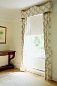 Hell gemusterter Vorhang mit passender Schabracke neben antikem Konsolentisch in traditionellem Wohnzimmer