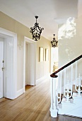 Wrought iron pendant lamps and wooden staircase with antique, carved balustrade in English house