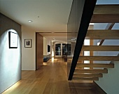 Floating staircase between wall and dark stringer element in wide hallway with view of open-plan living space