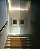 Open wooden stairs between wall with flush handrail in recess and shiny, black supporting wall