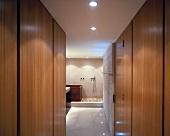View between wall units to wooden bathtub and shower area with wooden slatted floor in modern ensuite bathroom