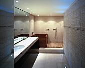 Edle Materialeinheit - Waschtisch aus Stein mit passenden Fliesen in verschiedenen Formaten und Holz in puristischem Designerbad