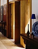 Sunshine on wooden doors between antique console tables with objets