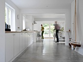 Woman in front of long kitchen unit and man in dining area of modern room with concrete floor
