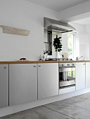 Modern, white kitchen units with wooden work surface, stainless steel oven, hob and extractor fan and concrete floor