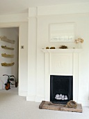 Traditional fireplace with natural finds and view into corridor with collection of boats and tricycle