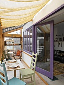 Conservatory with fabric sunshade and simple wooden furniture in front of living room with lilac window frames