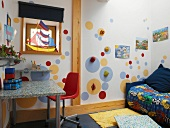 Colourful child's bedroom with sailing boat in window and slanting light from above falling on circles of colour with climbing holds
