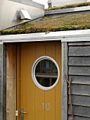 Front door with bulls-eye window beneath slanting turf roof