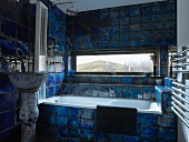 Bathroom with view of landscape through narrow, horizontal window and bold, mottled blue tiles